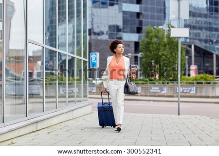 travel, business trip, people and tourism concept - young african american  woman with travel bag walking down city street - stock photo