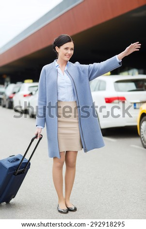 travel, business trip, people, gesture and tourism concept - smiling young woman with travel bag catching taxi at airport terminal or railway station - stock photo