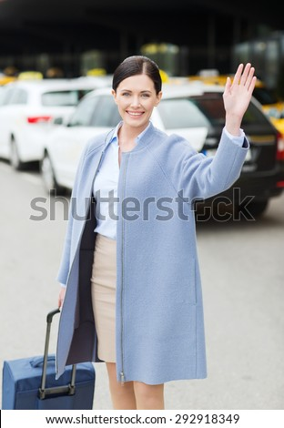 travel, business trip, people, gesture and tourism concept - smiling young woman with travel bag over taxi waving hand at airport terminal or railway station - stock photo