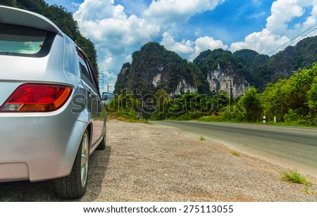 Travel by car. The car parked on the roadside, in front of the mountain with clouds - stock photo