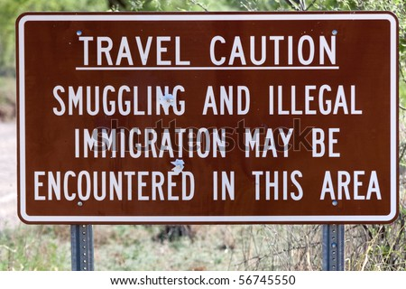 Travel caution sign warning of illegal activities with bullet holes