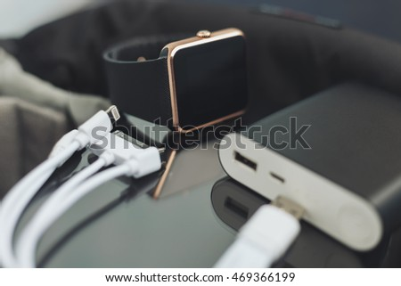 Travel charger and smart wrist watch and cable management for charge. This portable devices will let you stay connected to the internet and work. Fading film colors