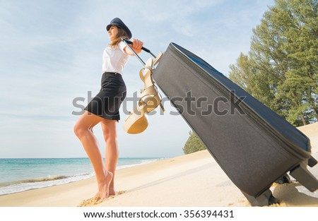 Travel concept. Attractive flight attendant with suitcase, hat and shoes on the beach. - stock photo