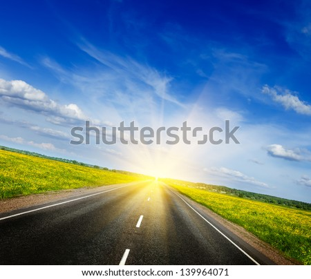 Travel concept background - road in blooming spring meadow on sunset - stock photo