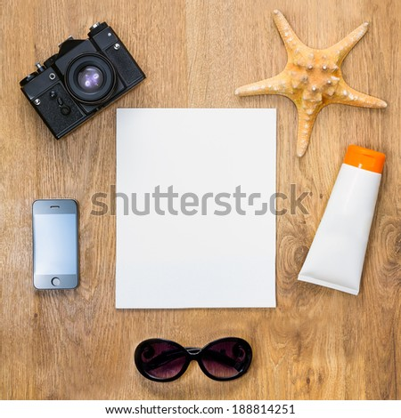 Travel concept collection. Top view of vintage camera, smartphone, sea star, tube with sunbathing cream, sunglasses and blank white paper on a wooden background.  - stock photo
