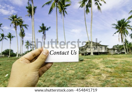 travel concept, cropped hand holding white canvas with word contact us over blurred background of rural area.wooden house surrounded by coconut tree at sunny day and cloudy blue sky - stock photo