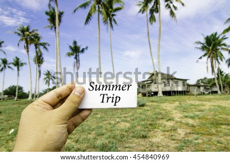 travel concept, cropped hand holding white canvas with word summer trip over blurred background of rural area.wooden house surrounded by coconut tree at sunny day and cloudy blue sky - stock photo