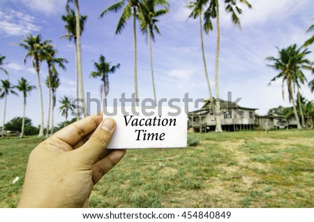travel concept, cropped hand holding white canvas with word vacation time over blurred background of rural area.wooden house surrounded by coconut tree at sunny day and cloudy blue sky - stock photo