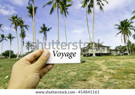 travel concept, cropped hand holding white canvas with word voyage time over blurred background of rural area.wooden house surrounded by coconut tree at sunny day and cloudy blue sky - stock photo
