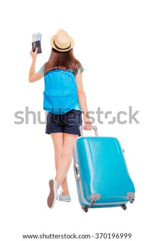 Travel concept. Full length studio portrait of  young woman holding passport with tickets walking with luggage. Isolated on white. - stock photo