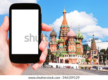travel concept - hand holds smartphone with cut out screen and Saint Basil Cathedral on Moscow Red Square on background - stock photo