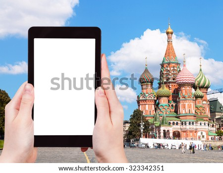 travel concept - hand holds tablet pc with cut out screen and Pokrovsky Cathedral on Red Square in Moscow on background - stock photo