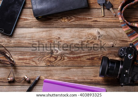 Travel concept - headphones, camera,  sketchbook, purse, pencil and keys on wooden background. Flat lay top view photo with copyspace in center. - stock photo