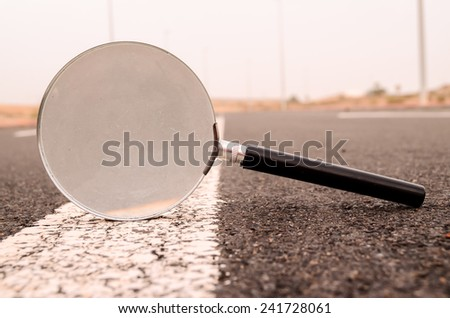 Travel Concept Magnify Glass Loupe on the Asphlat Road - stock photo