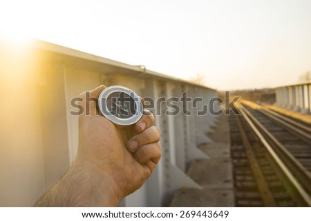 Travel Concept man hand hold metal modern Compass on wooden and metal railway in perspective background Empty space for inscription  - stock photo