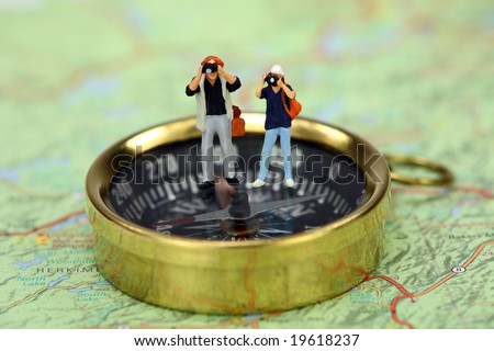 Travel concept. Miniature tourists taking pictures while standing on a compass. There is a map under the compass. - stock photo