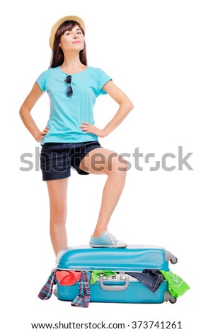 Travel concept. Studio portrait of young pretty woman trying to close her valise with cloth. Isolated on white.