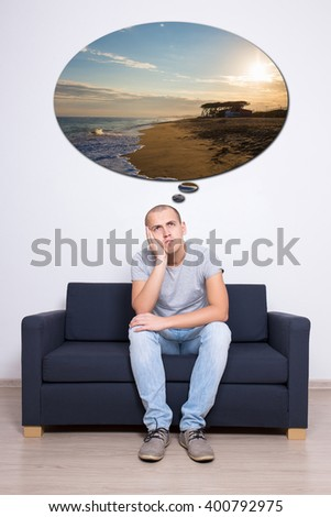 travel concept - thoughtful man sitting on sofa and dreaming about vacation - stock photo
