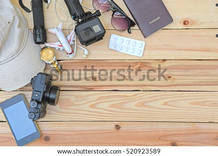 travel concept - top view of traveler's accessories and items with camera, medicine, sunglasses, hat, flashlight, watch, passport on wooden background