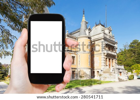 travel concept - tourist photograph Masandra Palace of Emperor Alexander III in Crimea on smartphone with cut out screen with blank place for advertising logo - stock photo