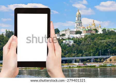 travel concept - tourist photograph riverside view of Kiev Pechersk Lavra, Kiev, Ukraine on tablet pc with cut out screen with blank place for advertising logo - stock photo