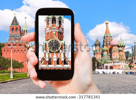 travel concept - tourist photographs picture of Spasskaya Tower and Red Square of Moscow Kremlin on smartphone - stock photo