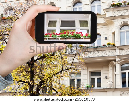 travel concept - tourist takes picture facade of house and yellow linden in Berlin in autumn on smartphone, - stock photo