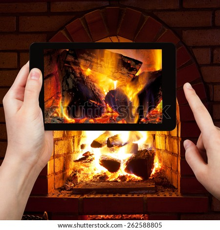 travel concept - tourist takes picture of burning wood in fireplace in evening time on smartphone,