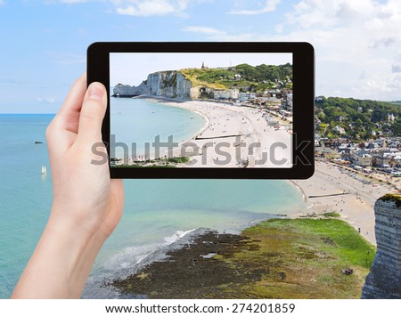 travel concept - tourist takes picture of Etretat resort village on english channel beach of cote d'albatre, France on tablet pc - stock photo