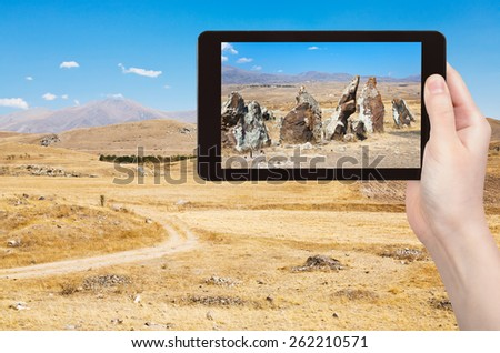 travel concept - tourist takes picture of megalithic standing stone of Zorats Karer (Carahunge) - pre-history monument in Armenia on smartphone, - stock photo