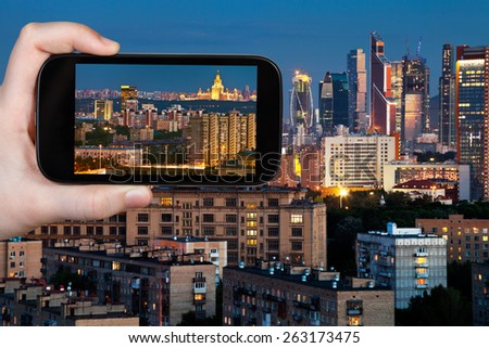 travel concept - tourist takes picture of panorama of Moscow city in blue summer night on smartphone, - stock photo