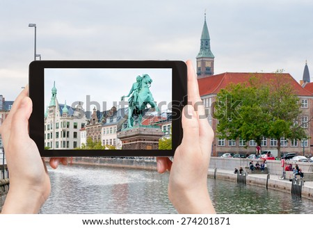 travel concept - tourist takes picture of Statue of Absalon on Hojbro square and Frederiksholms Kanal in Copenhagen, Denmark on tablet pc - stock photo