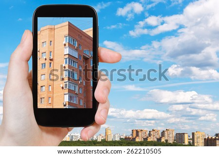 travel concept - tourist takes picture of urban apartment brick house in spring day on smartphone, Moscow, Russia - stock photo