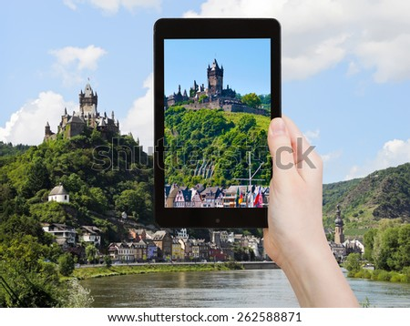 travel concept - tourist takes picture of view of Cochem town on Moselle river and Cochem Imperial castle over town in Germany on smartphone, - stock photo