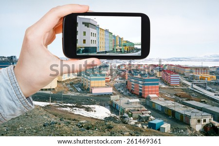 travel concept - tourist taking photo of Anadyr town on mobile gadget in spring, Chukotka, Russia - stock photo