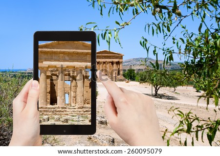 travel concept - tourist taking photo of ancient Temple of Concordia in Valley of the Temples, Agrigento, Sicily on mobile gadget - stock photo