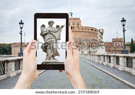 travel concept - tourist taking photo of Angel statue on St Angel Bridge on mobile gadget, Rome, Italy - stock photo