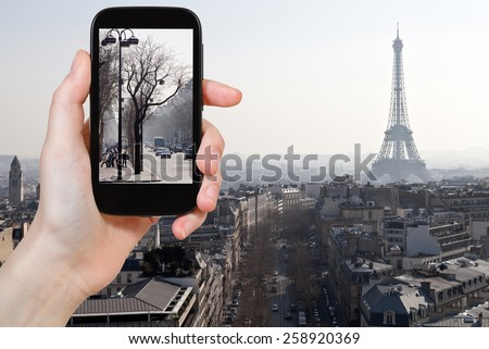 travel concept - tourist taking photo of Avenues in Paris in early spring on mobile gadget, France - stock photo