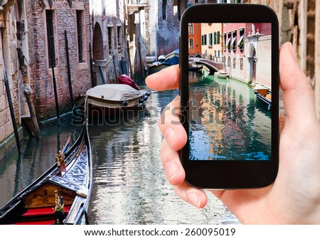 travel concept - tourist taking photo of canal, gondola, boats in Venice, Italy on mobile gadget - stock photo