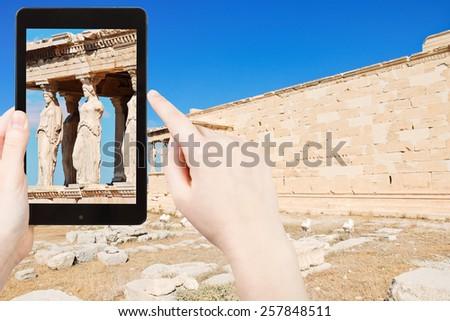 travel concept - tourist taking photo of caryatids at acropolis on mobile gadget, Athens, Greece - stock photo