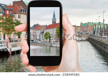 travel concept - tourist taking photo of Copenhagen cityscape on mobile gadget, Denmark - stock photo