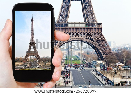 travel concept - tourist taking photo of Eiffel tower in Paris from Trocadero on mobile gadget, France - stock photo