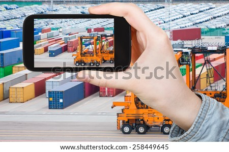 travel concept - tourist taking photo of freight containers in Copenhagen cargo port on mobile gadget - stock photo