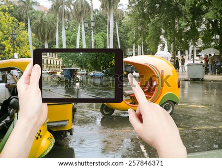travel concept - tourist taking photo of Havana street in rain on mobile gadget, Cuba - stock photo