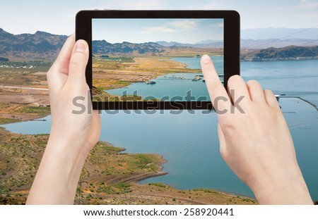 travel concept - tourist taking photo of Lake Mead in Nevada on mobile gadget, Nevada, USA - stock photo