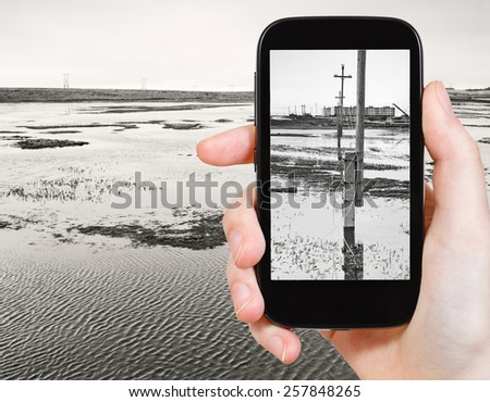 travel concept - tourist taking photo of melted snow in tundra in spring on mobile gadget, Anadyr, Chukotka, Russia - stock photo