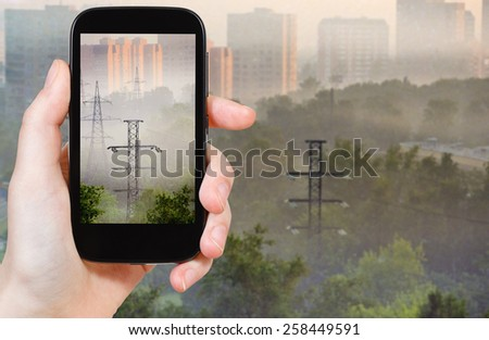 travel concept - tourist taking photo of morning fog in industrial city on mobile gadget - stock photo