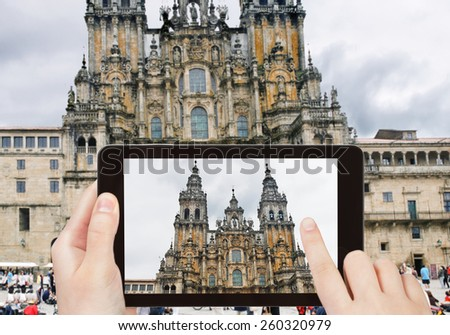 travel concept - tourist taking photo of The Cathedral of Santiago de Compostela on mobile gadget, Spain - stock photo