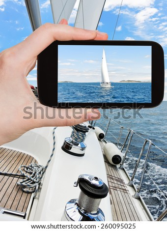 travel concept - tourist taking photo of white sail yacht in blue Adriatic sea, Dalmatia, Croatia on mobile gadget - stock photo