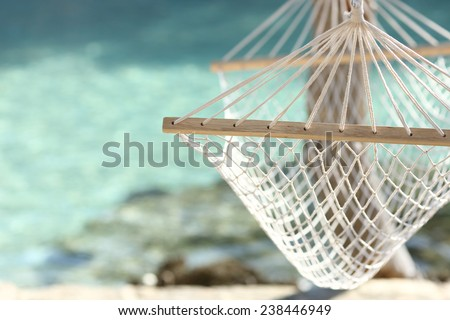 Travel concept with a hammock in a tropical beach with turquoise water in the background - stock photo